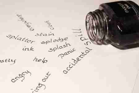 precise writing - - ink bottle spills out on the paper a lot of words